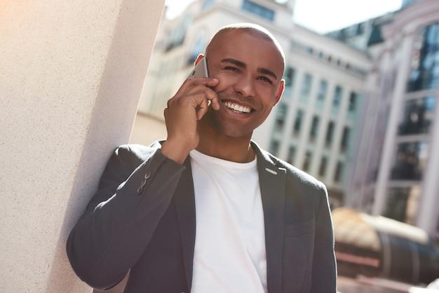 Telefonema jovem parado na rua da cidade conversando com um amigo no smartphone sorrindo