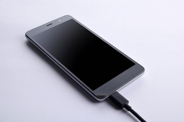 Telefones inteligentes móveis cobrando sobre fundo branco de mesa de madeira