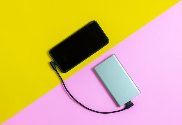 Telefones móveis de smartphone que cobram baterias pelo fundo cor-de-rosa e amarelo do banco do poder