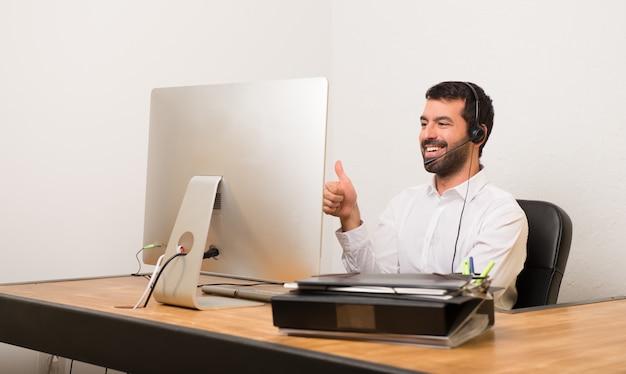Telemarketer homem em um escritório dando um polegar para cima gesto porque algo bom aconteceu