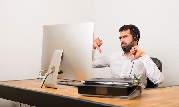 Telemarketer homem em um escritório mostrando o polegar para baixo com as duas mãos