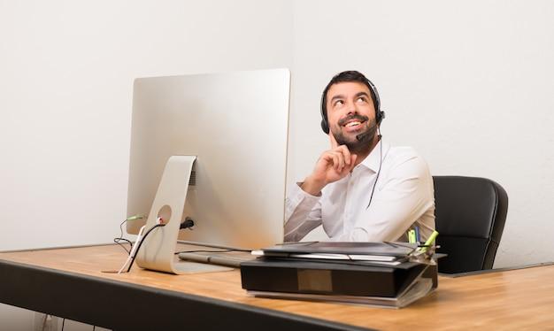 Telemarketer homem em um escritório pensando uma idéia ao olhar para cima