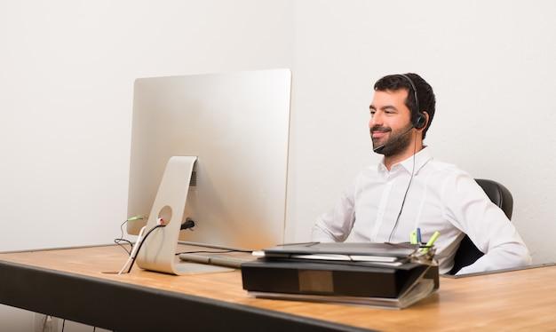 Telemarketer homem em um escritório posando com os braços no quadril e rindo olhando para a frente