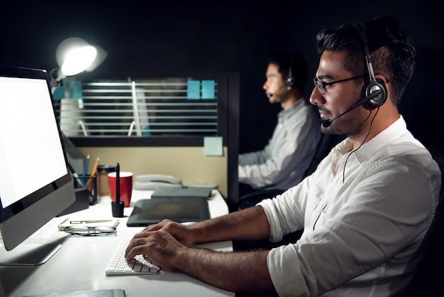 Telemarketers de atendimento ao cliente asiático masculino trabalhando turno da noite em call center