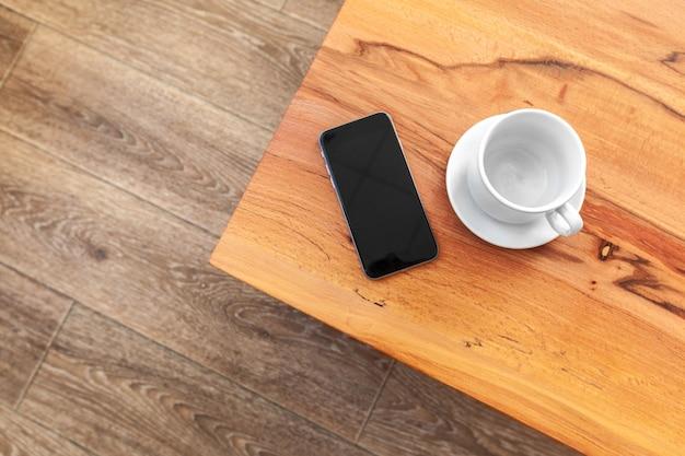 Telemóvel com maquete de tela em branco na mesa de madeira