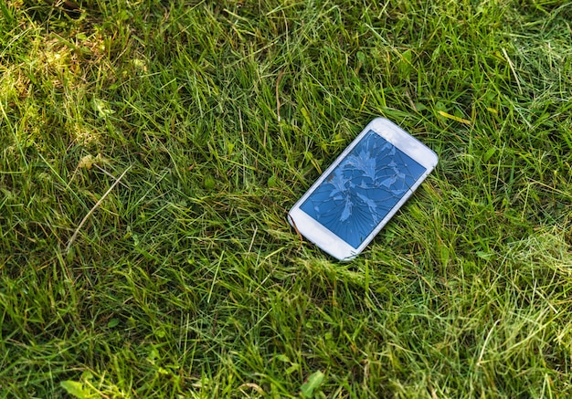 Telemóvel quebrado com indicador rachado no fundo da grama verde, ao ar livre.