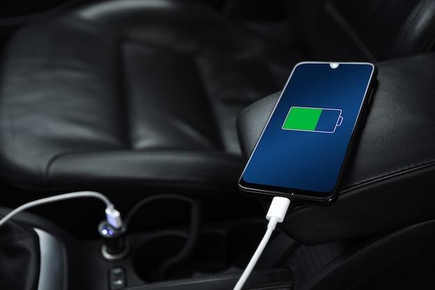 Telemóvel, smartphone, telemóvel carregado, carregue a bateria com o carregador usb no interior do carro. interior de carro preto moderno
