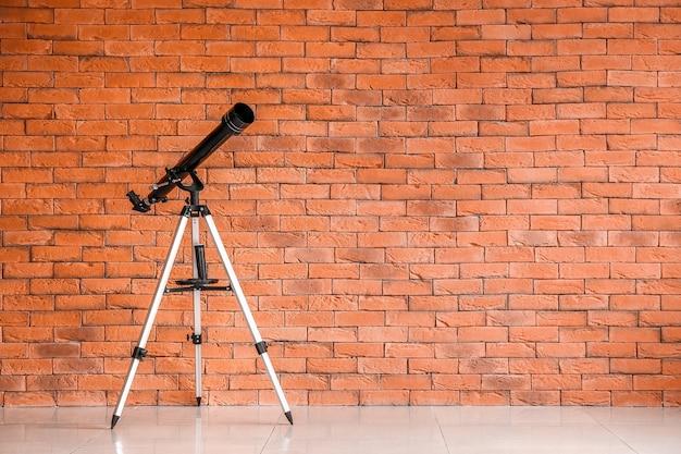 Telescópio moderno perto da parede de tijolos na sala
