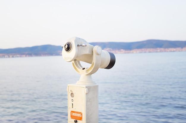 Telescópio no mar-verão, sol, praia do mar
