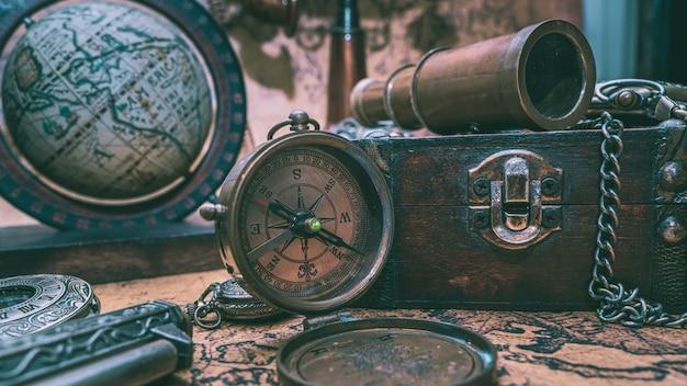 Telescópio vintage, bússola e antiga coleção no peito de madeira