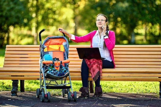 Teletrabalho de mulher com bebê no carrinho de bebê com ajuda de laptop ao ar livre