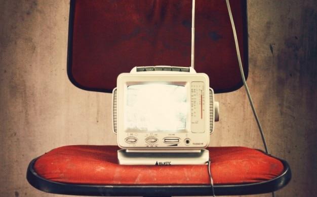 Televisão velho na cadeira vermelha
