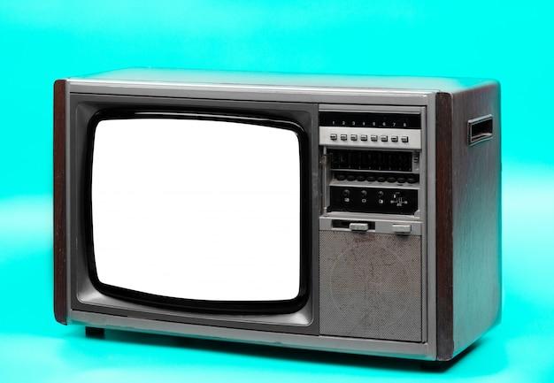 Televisão vintage com tela cortada sobre fundo verde.