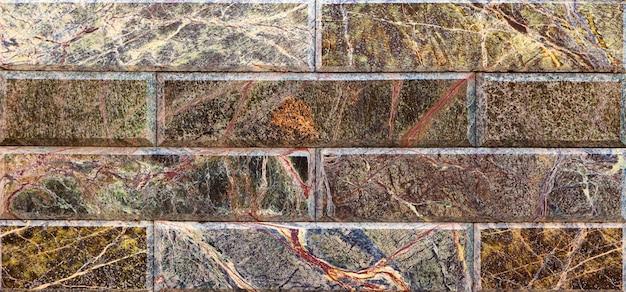 Telha de mármore de fundo, amarelo em forma de tijolos, com listras multicoloridas.