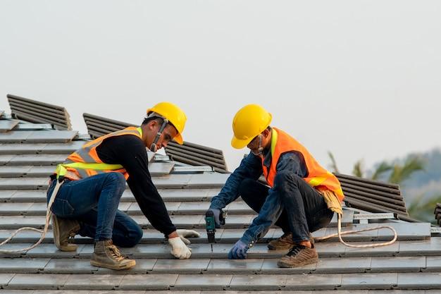 Telhadista usando pistola de pregos pneumática ou pneumática e instalando telha de concreto no telhado novo.