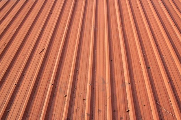 Telhado alaranjado da tampa a textura suja exterior do telhado, telhado home do metal do grunge.