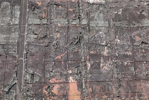 Telhado antigo coberto de resina, que começou a se quebrar e descascar