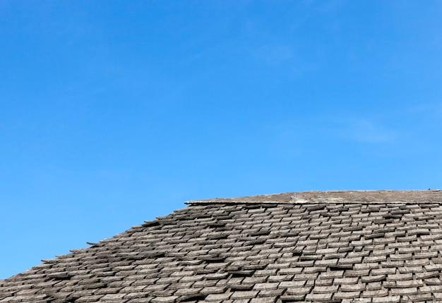 Telhado antigo feito de pequenas placas cinza contra o céu azul