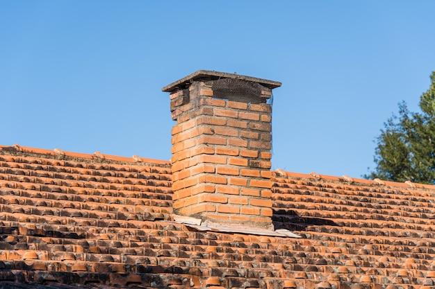 Telhado com telhas e chaminé vermelha no interior do brasil. nas árvores de fundo e no céu azul.