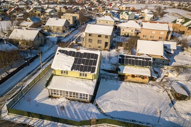 Telhado da casa coberto com painéis solares no inverno com neve no topo