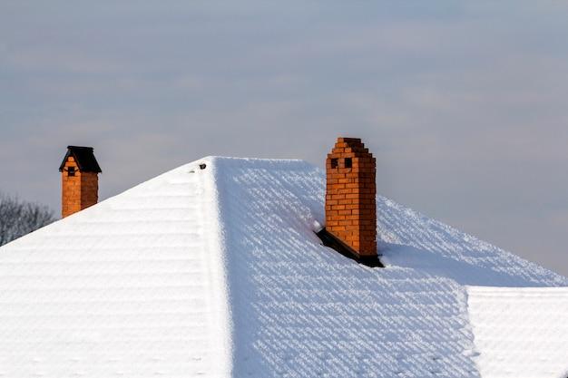 Telhado da casa com chaminés de tijolos cobertos de neve no inverno