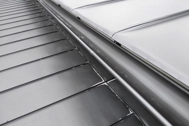Telhado da casa feito de chapas de metal cinza.