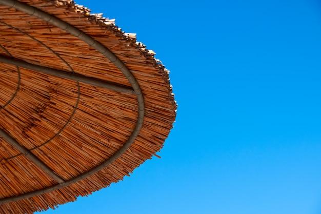 Telhado da palha do guarda-chuva de sol, céu azul. tópico de férias. praia de verão.