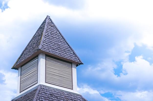 Telhado de casa de madeira com clarabóia triangular com céu azul, detalhe de uma construção de casas de madeira com telhado de estilo asiático