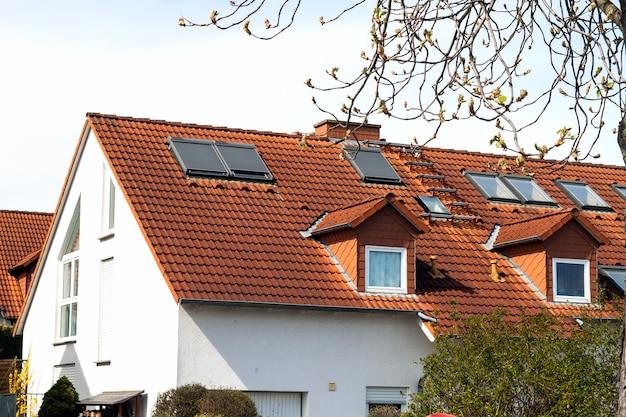 Telhado de casas residenciais clássicas com telhas e janelas laranja