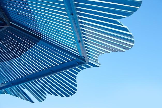 Telhado de gazebo de madeira branco no parque contra um fundo de céu azul com espaço para seu texto