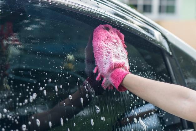 Telhado de lavagem do carro da mulher asiática com pano do microfiber.