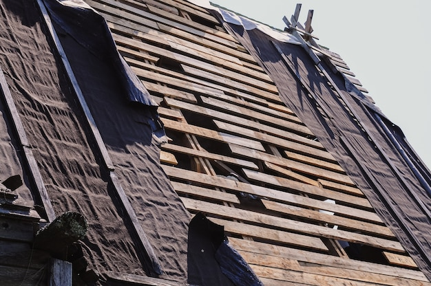 Telhado de tábua de madeira quebrado e material de telhado rasgado de uma casa velha na vila precisam de reparos