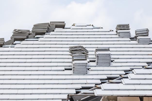 Telhado de telha cor cinza concreto em construção com pilhas no telhado