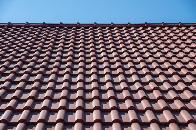 Telhado de telha marrom sob o céu azul.