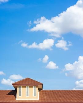 Telhado de uma casa destacada com céu azul e nuvem.