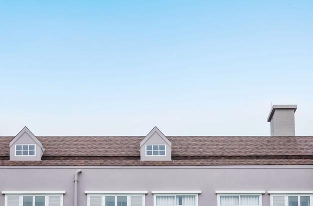 Telhado do close up do edifício com espaço da cópia no fundo do céu azul