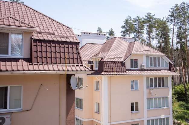 Telhado em propriedade residencial com novas telhas de metal ondulado marrom. telhado de metal moderno. coberturas metálicas.