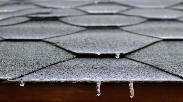 Telhado no telhado de uma casa ou gazebo feito de telhas betuminosas com água corrente congelada e pingentes de gelo pendurados. fechar-se.
