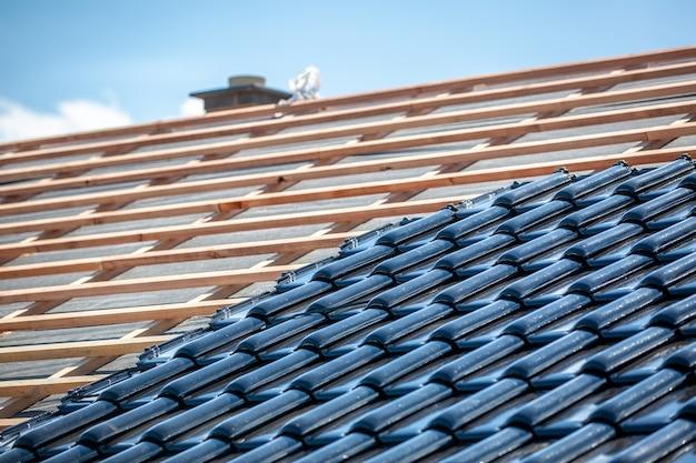 Telhado preto de telhas queimadas sob a construção, pavimentador de telhado