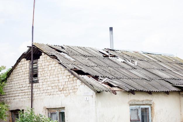 Telhado quebrado depois de um furacão, uma casa na aldeia, o telhado destruído de uma casa residencial