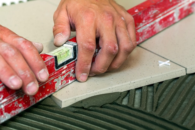 Telhas cerâmicas e ferramentas para ladrilhador. mão de trabalhador, instalação de pisos. melhoria home, renovação - adesivo para piso de cerâmica, argamassa, nível.