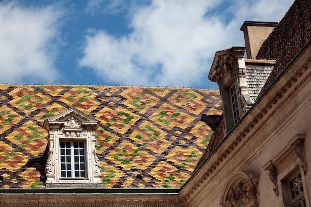 Telhas de telhado cerâmicas tradicionais em uma construção do governo em dijon, borgonha, frança.
