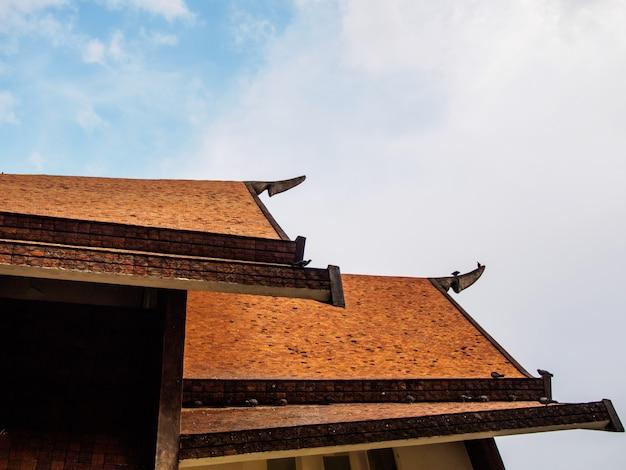 Telhas de telhado tradicionais tailandesas no fundo do céu azul