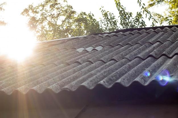 Telhas e luz solar do céu no fundo