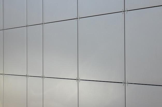 Telhas quadradas cinza limpas suaves brilhantes na parede