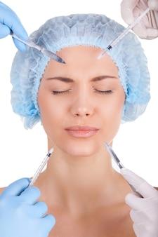Tem certeza? mulher jovem assustada mantendo os olhos fechados enquanto quatro mãos em luvas médicas segurando seringas e facas perto do rosto