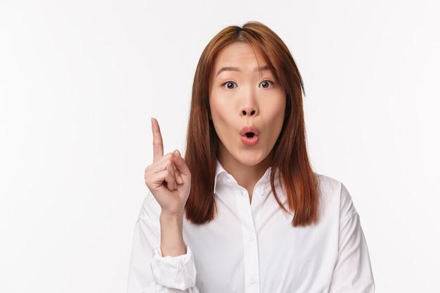 Tem solução. o retrato do close-up da mulher asiática criativa animada sugere a idéia, dobrando os lábios como dizendo algo, levante o gesto de eureka do dedo, faça um bom argumento, fique