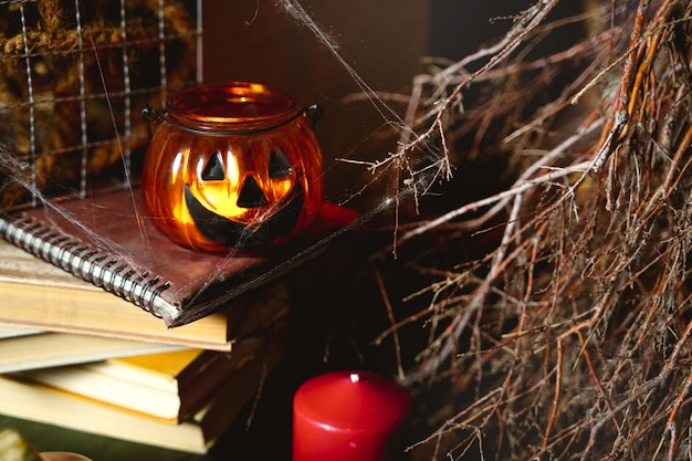 Tema colorido da natureza morta para o livro escuro assustador do dia das bruxas coberto com teias de aranha queimando a abóbora ...