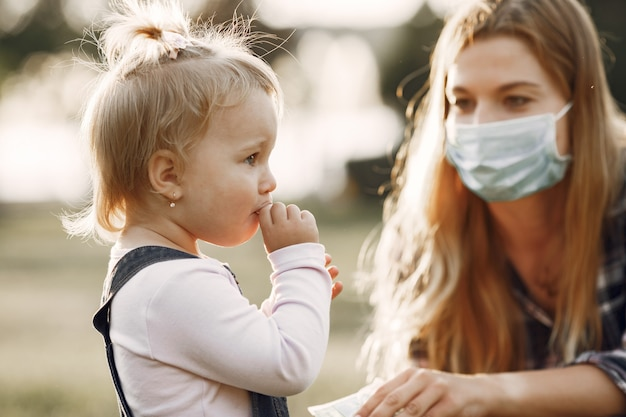 Tema coronavirus. família em um parque de verão. mulher com uma camisa de cela.