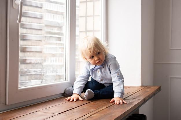 Tema coronavirus. ficar em casa. adorável garoto loiro menino sentado no parapeito da janela.